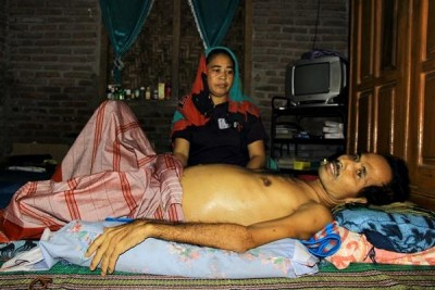 Karim terbaring ditemani istrinya Siti Suwarni. Foto: Bin