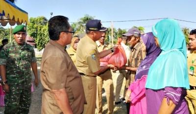 Wakil Walikota Bima saat menyerahkan sembako bersubsidi pada operasi pasar murah. Foto: Hum