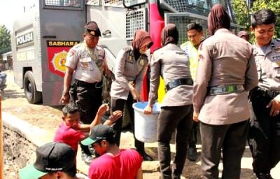 Personil Polres Bima Kabupaten saat distribusi air. Foto: Bin