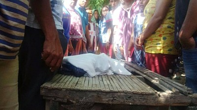 Bayi dibungkus kain saatb disaksikan warga setempat. Foto: Bin