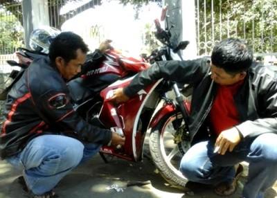 Beri bersama Ujang mencopot stiker Nomor Urut 3 yang menempel pada sepeda motor mereka. Foto: Ady