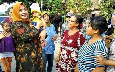 DINDA saat menggendong bocah warga setempat. Foto: Teta