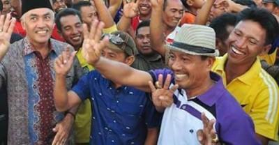 Camat Woha yang mengenakan topi putih sedang mengangkat tangan tanda nomor urut pasangan DINDA.