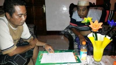 Sirajudin (Kiri) saat difoto menandatangani perjanjian pinjam uang dengan orang tua Adhar
