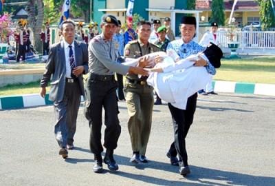 Anggota Paskibraka pingsan dan ditandu keluar lapangan. Foto: Ady