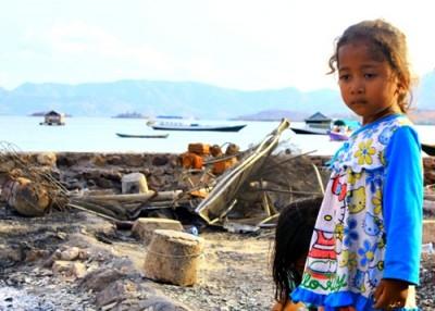 Seorang anak saat menyaksikan sisa kebakaran. Foto: Bin