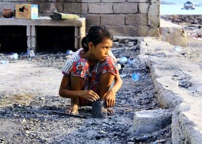 Wanti, saat merapikan sisa sisa kebakaran di halaman rumahnya. Foto: Bin