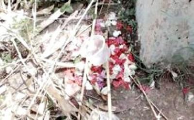 TKP yang ditaburi bunga dan gelas plastik.