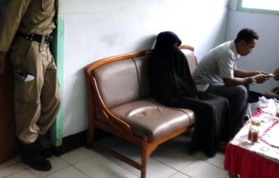 Iwe, wanita berjubah hitam saat diamankan di kantor Sat Pol PP Kota Bima. Foto: Deno