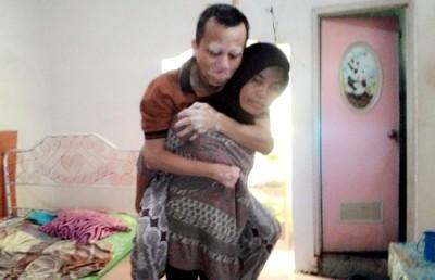 Sri saat menggendong suaminya untuk diantar keluar masuk kamar mandi.
