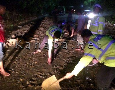 Polisi saat membersihkan lumpur dan kerikil. Foto: Deno