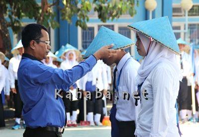 Ketua STIE Bima Firdaus saat memasang topi kepada mahasiswa sebagai tanda dimulainya kegiatan PKMMB. Foto: Bin