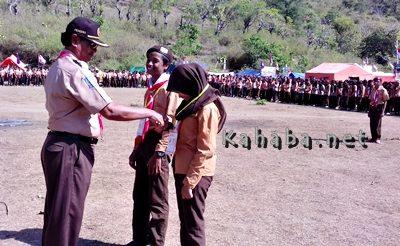 Wakil Ketua Kwarcab Pramuka Kota Bima saat mengalungkan tanda peserta kemah. Foto: Eric