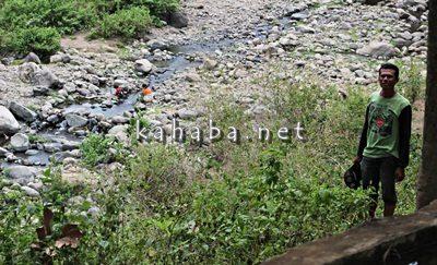 Sekdes Ntoke berdiri di sungai, akses jalan di Dusun Ropo. Foto: Bin