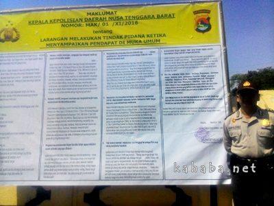 Kasubbag Humas Polres Bima Kota IPDA. Suratno saat berdiri samping spanduk maklumat larangan melakukan tindak pidana saat menyampaikan pendapat didepan  umum. Foto: Ompu