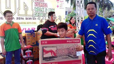 Manager Hokky Mart Hendra Rusli didampingi Ketua STIE Bima Firdaus MM, saat Menyerahkan Hadiah Televisi Kepada Peserta Fun Bike. Foto: Eric