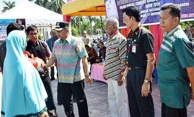 Wakil Walikota Bima saat menyerahkan Sembako kepada warga saat operasi pasar murah. Foto: Hum