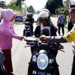 Siswa TK Bhayangkari Bagikan Helm dan Coklat Pada Pengendara